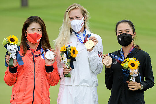 Gold medallist Nelly Korda shares the podium with Japan's Mone Inami (L) and Lydia Ko