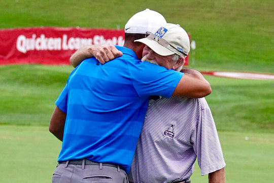 Fluff and Tiger Woods hug it out at the Quicken Loans National (Credit: PGA Tour)